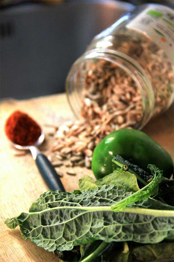 Semi di girasile rovesciati su un tagliere con accanto un cucchiaio di paprika, in primo piano cavolo nero e peperone verde.