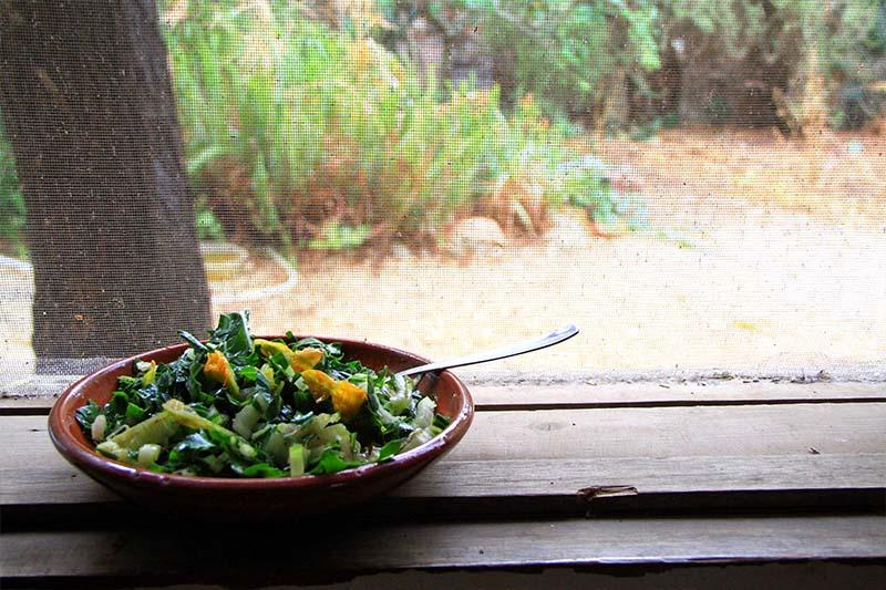 Una ciotola di coccio contenente l'insalata, posta sul davanzale di una finestra