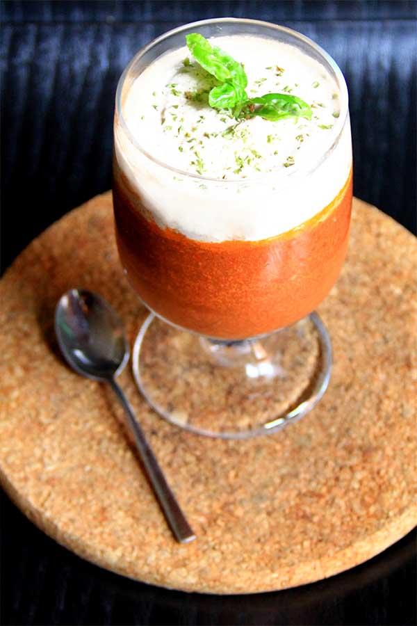 Mousse all'interno di un bicchiere di vetro. Si vedono due strati, quello più basso del pomodoro e quello superiore della salsa di cipolle.