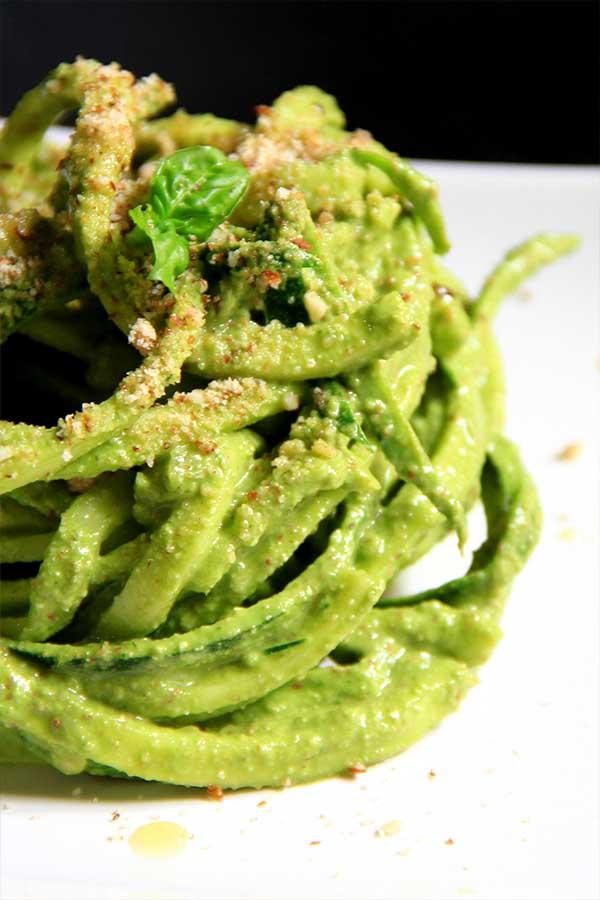 Spaghetti di zucchina arrotolati su un piatto bianco.