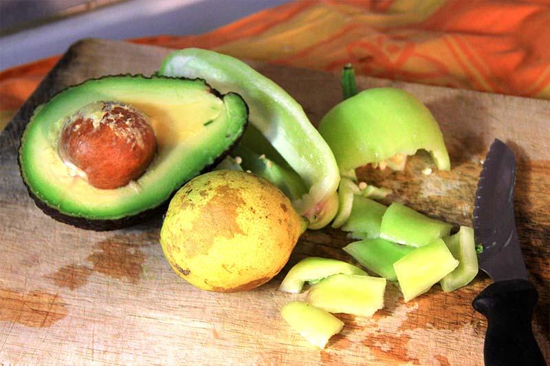 Mezzo avocado, un limone, e un peperone tagliato a quadratoni tutto su un tagliere