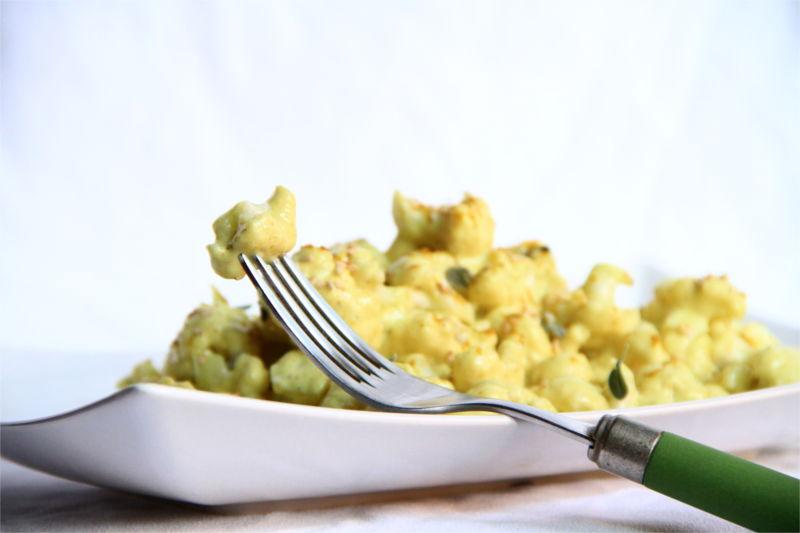 Cavolfiore alla crema di curry decorato con foglioline di maggiorana e semi di sesamo. In primo piano una forchetta che tiene un boccone.