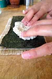 Due mani stendono il composto di cavolfiore sull'alga nori