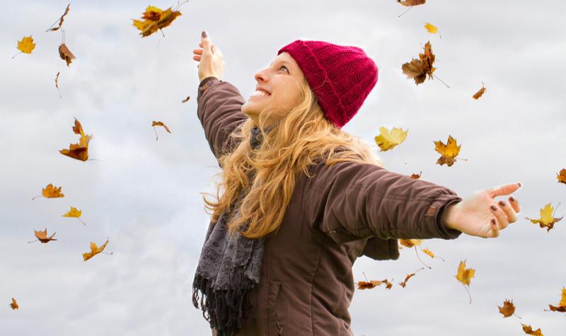 Una ragazza a braccia aperte ride mentre cadono le foglie