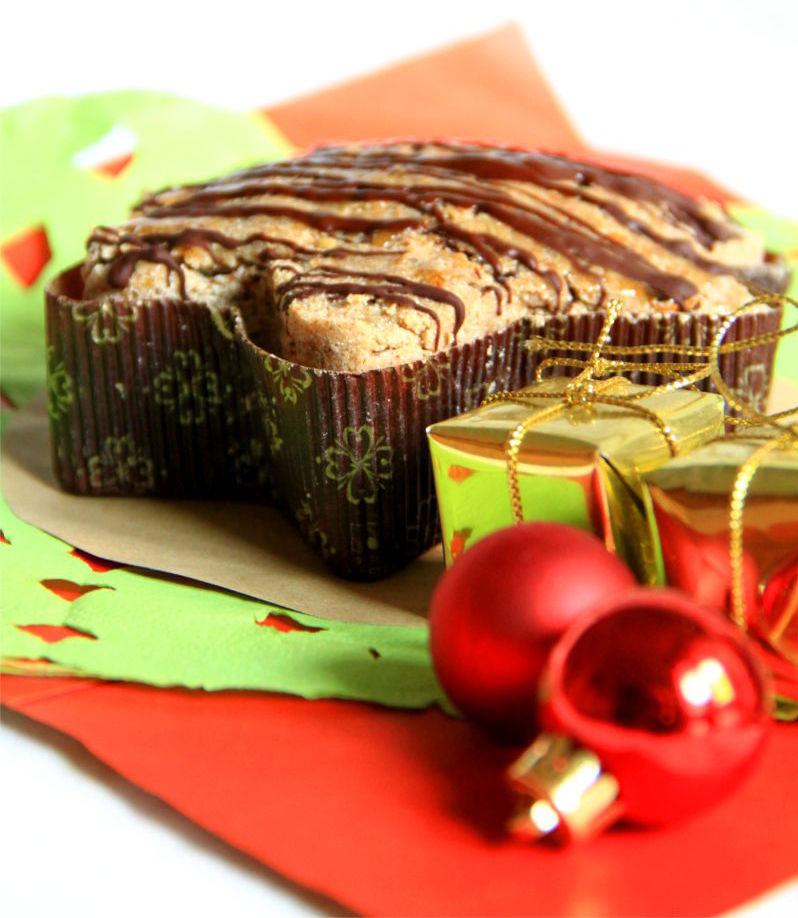 Pandoro al cioccolato crudista a forma di stella dentro l'involucro di carta. Accanto alcune decorazioni natalizie