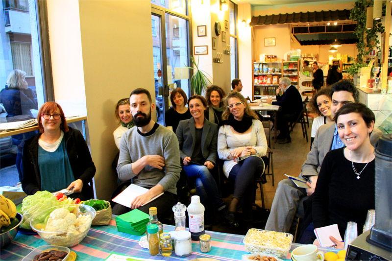 Varie persone sedute all'interno di un locale che aspettano l'inizio del corso