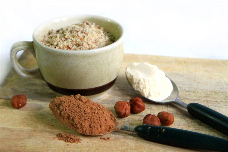 Una tazza di farina di nocciole, un cucchiaio di cacao, un cucchiaio di farina di cocco, qualche mandorle, tutto su un tagliere