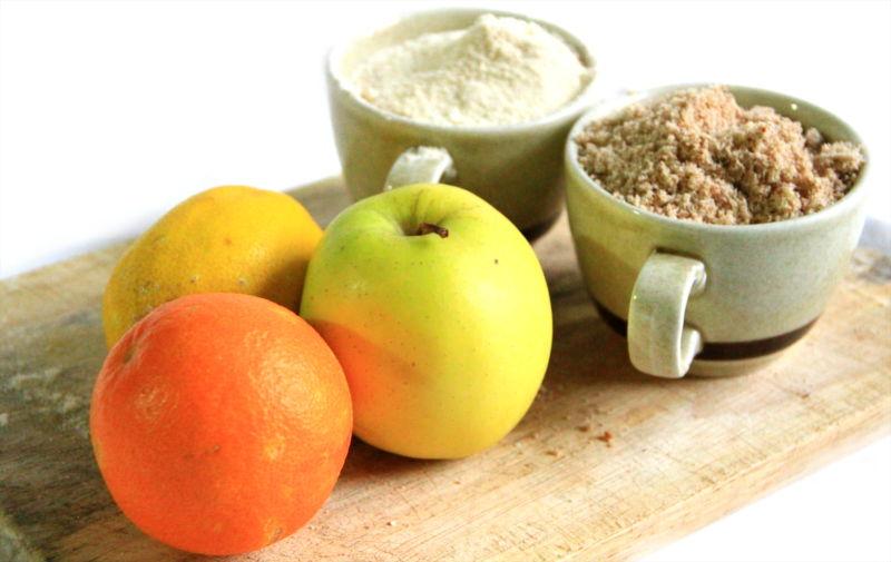 Un'aranci, una mela, un limone e due tazze di farine crudiste