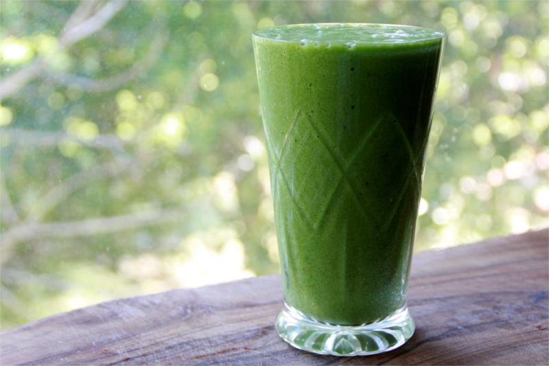 Un bicchiere di vetro pieno di Smoothie verde