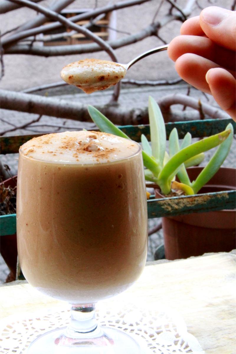Un bicchiere con una mousse di pera spolverata di cannella. Una mano solleva un cucchiaino di crema