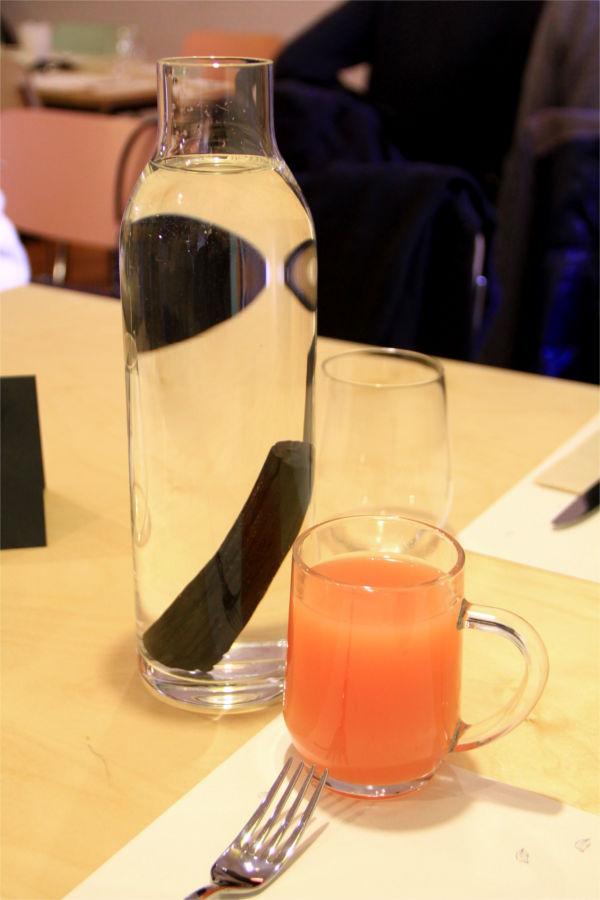 Una bottiglia di vetro con all'interno un bastoncino di carbone attivo e un bicchiere di estratto