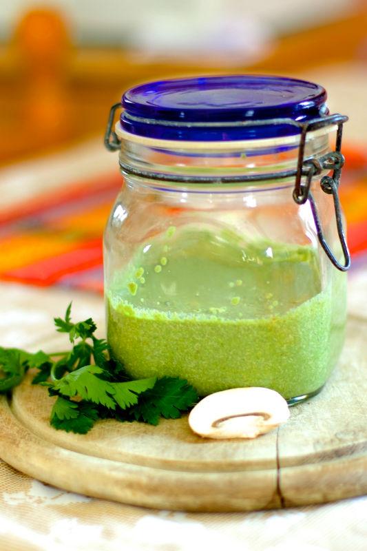 Un barattolo di salsa verde con accanto del coriandolo e funghi freschi