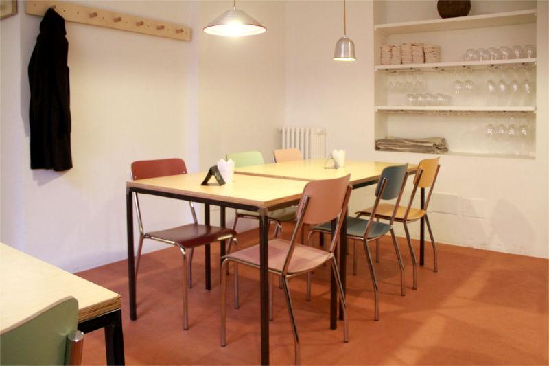 Interno del locale Mantra, tavoli in legno, sedie colorate
