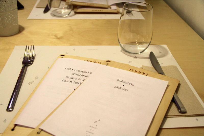 Menù Mantra sul tavolo, accanto bicchiere e posate