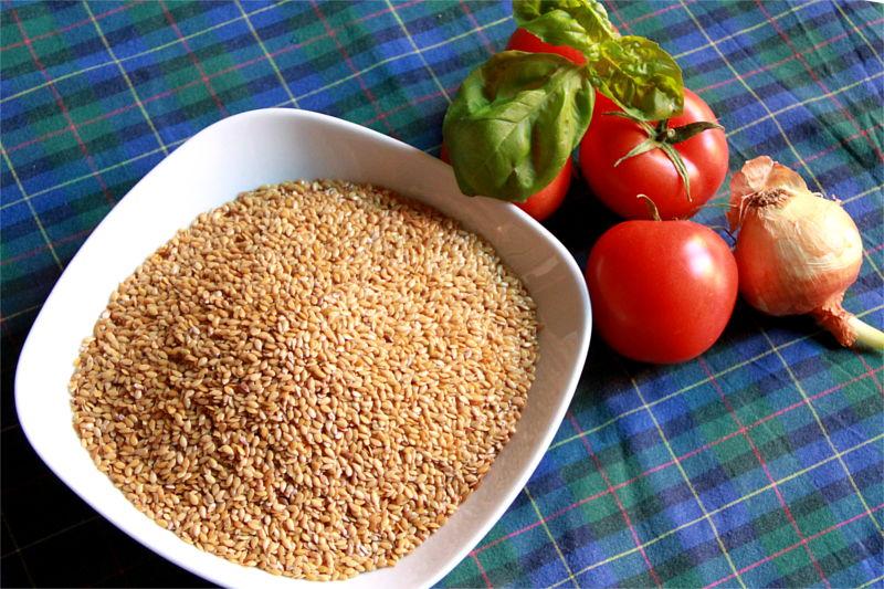 Un piatto con semi di lino. Accanto alcuni pomodori, basilico e una cipolla su tovaglia blu a righe.