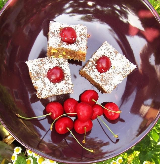 Un piatto scuro con all'interno dei quadrotti di dolcetti alle ciliegie.