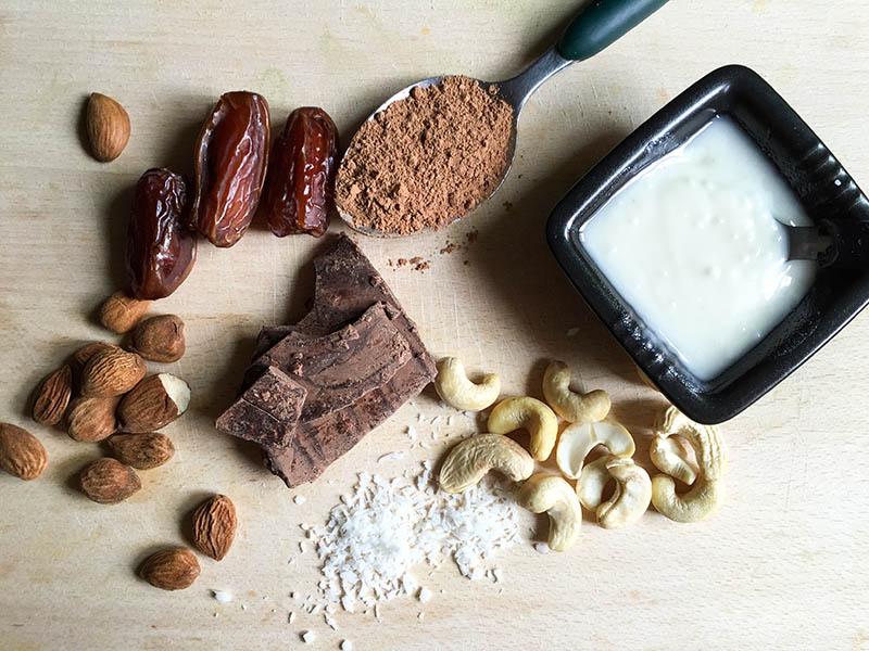 Vari ingredienti sul tagliare: anacardi, burro di cocco, cacao, cocco in scaglie, pasta di cacao, mandorle, datteri.