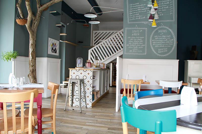 Interno del locale Romeow: alcuni tavoli e sedie colorati, il bancone di ingressi e il tronco di un albero.
