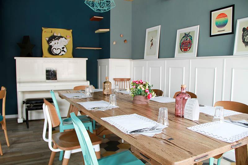 Interno del locale Romeow: un grande tavolo apparecchiato, varie sedie colorate e vari quadri alle pareti