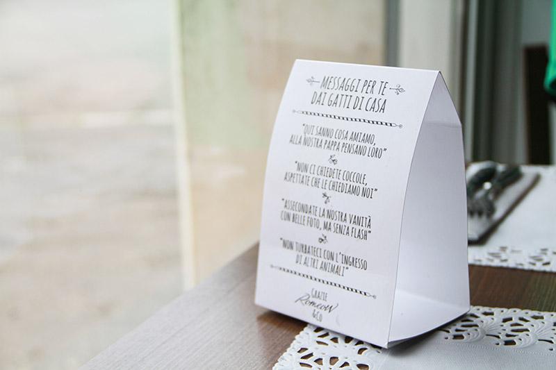 Un cartellino bianco sul tavolo con le Regole di Romeow cat Bistrot