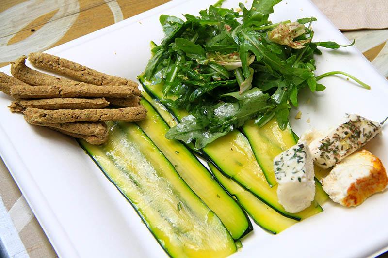 Un piatto con carpaccio di zucchine, grissini, rucola e formaggi crudisti