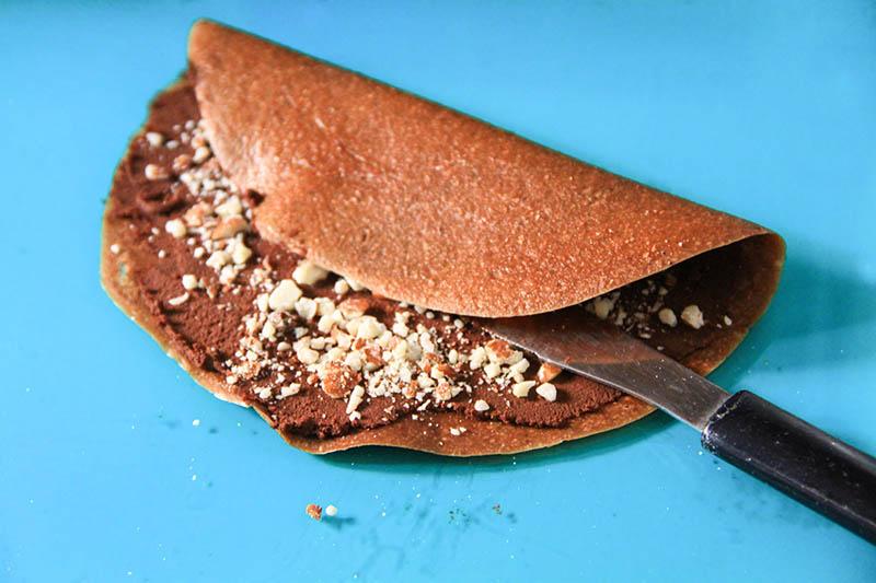 Una Crepes crudiste con cioccolato e granella di mandorle