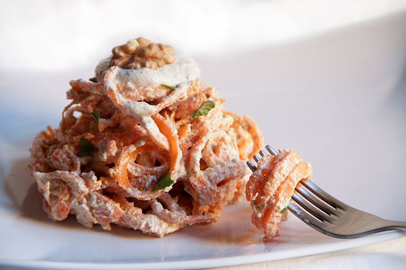Spaghetti di carote al pesto di noci su sfondo bianco