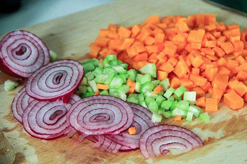 Su un tagliere Cipolle sedano e carote.