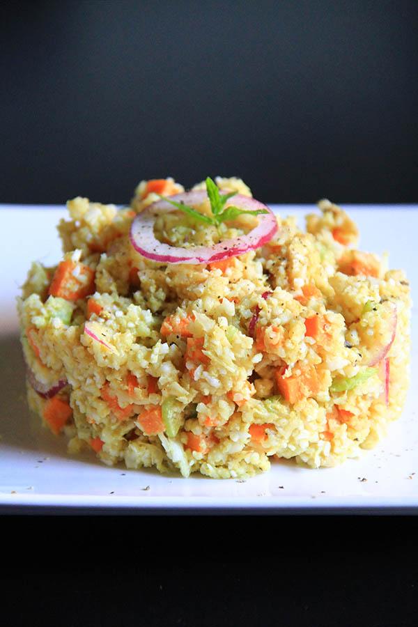 Al centro di un piatto bianco un tortino di cous cous di verdure.