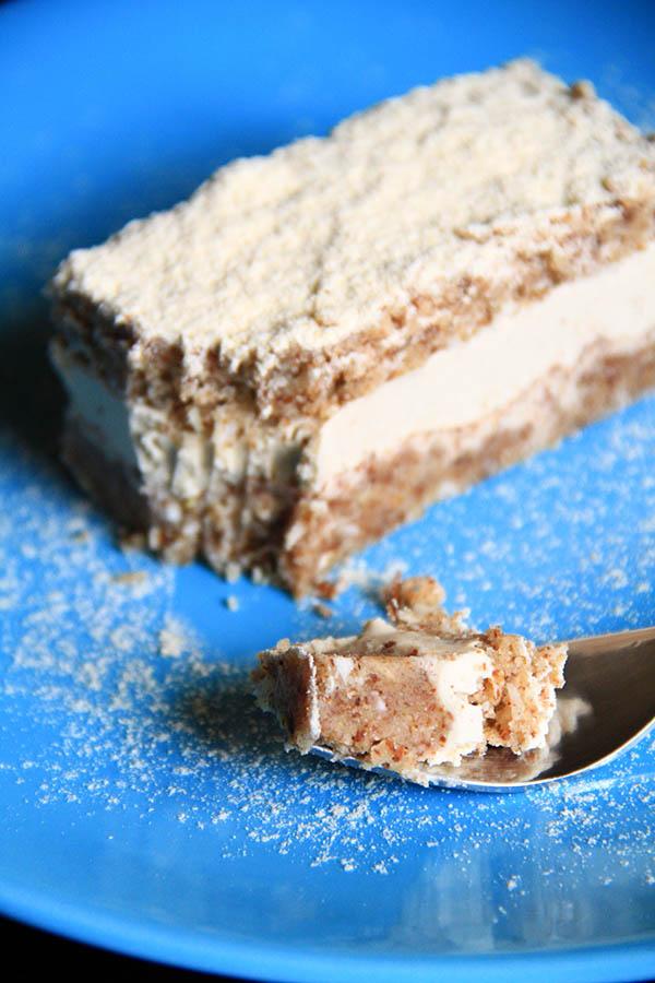 Una fetta di Torta Paradiso crudista all'interno di un piatto azzurro. In primo piano una forchetta con parte del dolce.