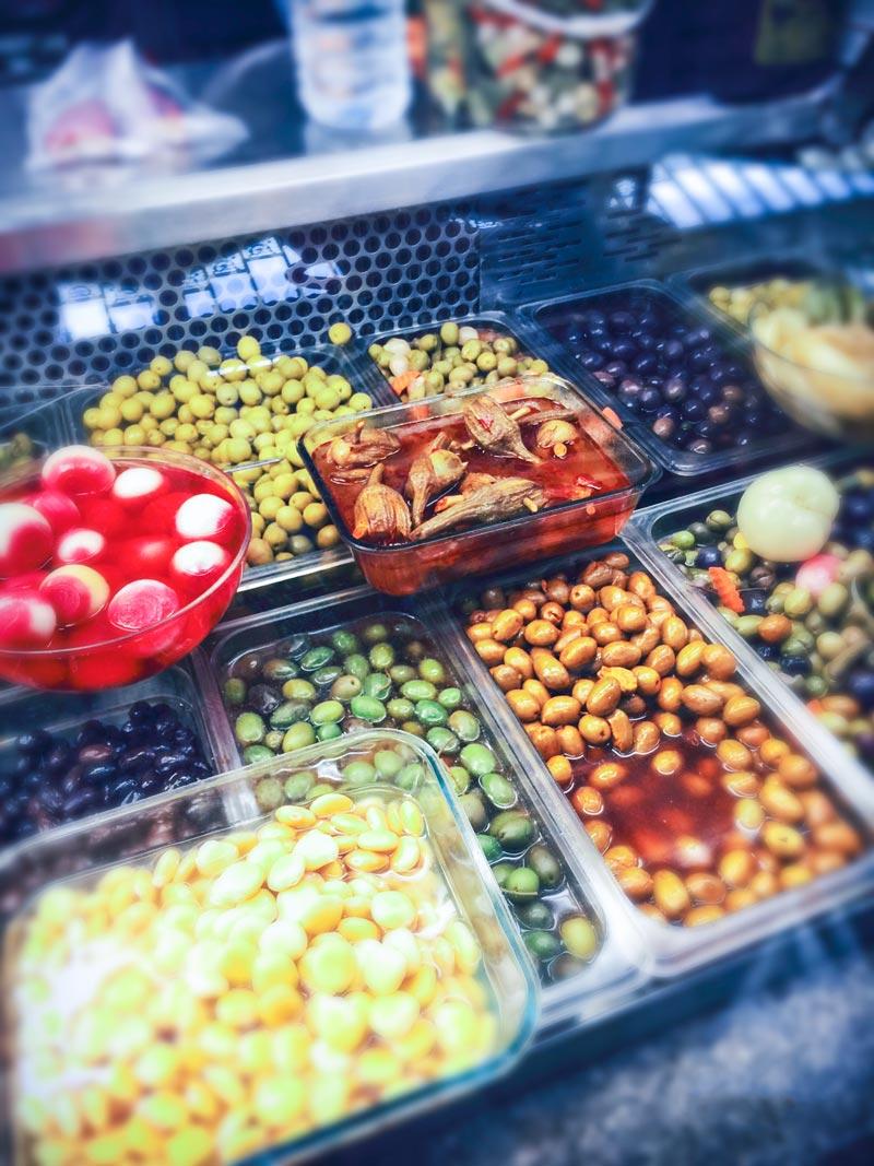 Un banco frigo propone melanzane, cipolle, olive e altri prodotti