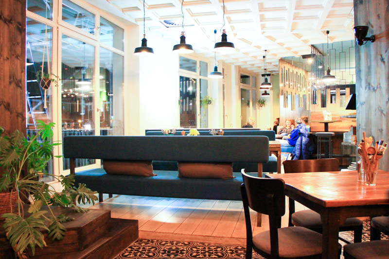 area salotto del locale, con divanetti di colore scuro, cuscini e fiori sui tavoli