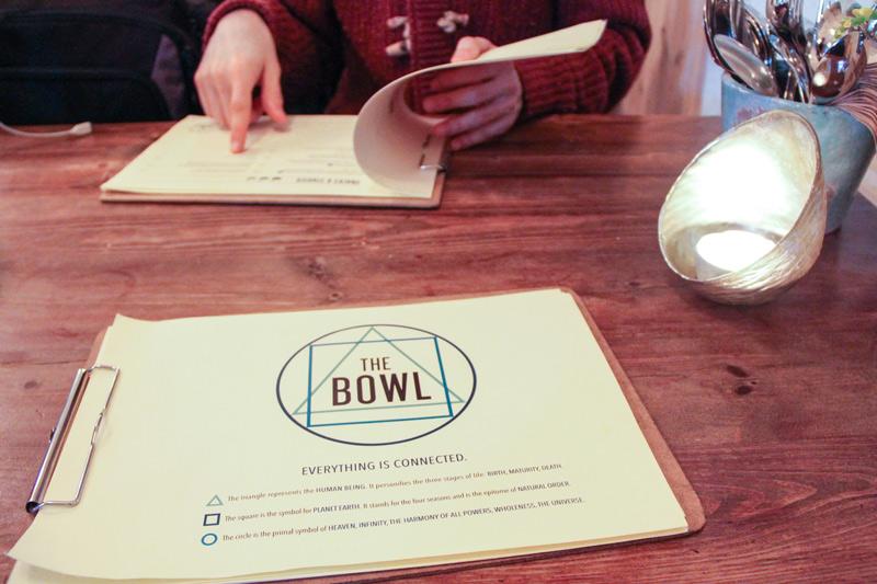 Il menù del locale presentato su una tavoletta di legno con clip