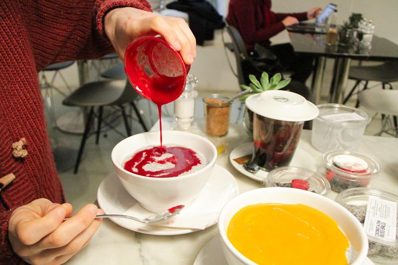 dressing di frutti rossi che viene versato su pudding di chia