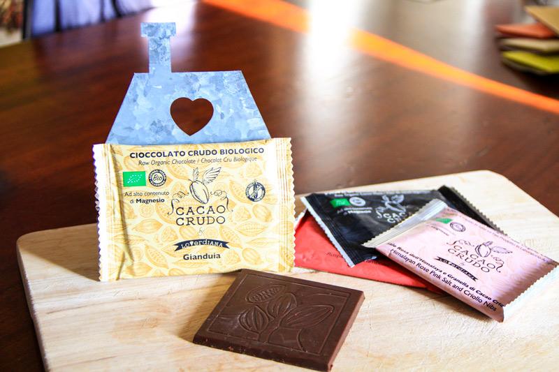 Una tavoletta quadrata di cioccolato sopra a un tagliere con il suo involucro ben mostrato